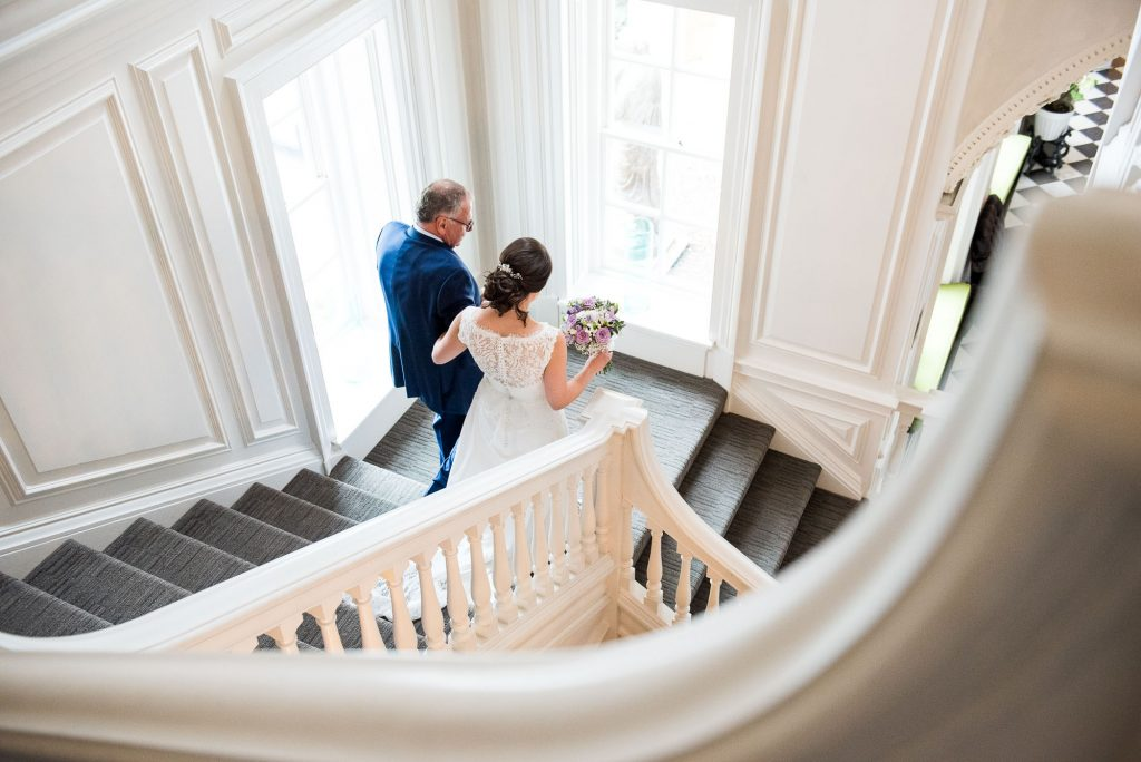 Bridal entrance down grand staircase Surrey wedding