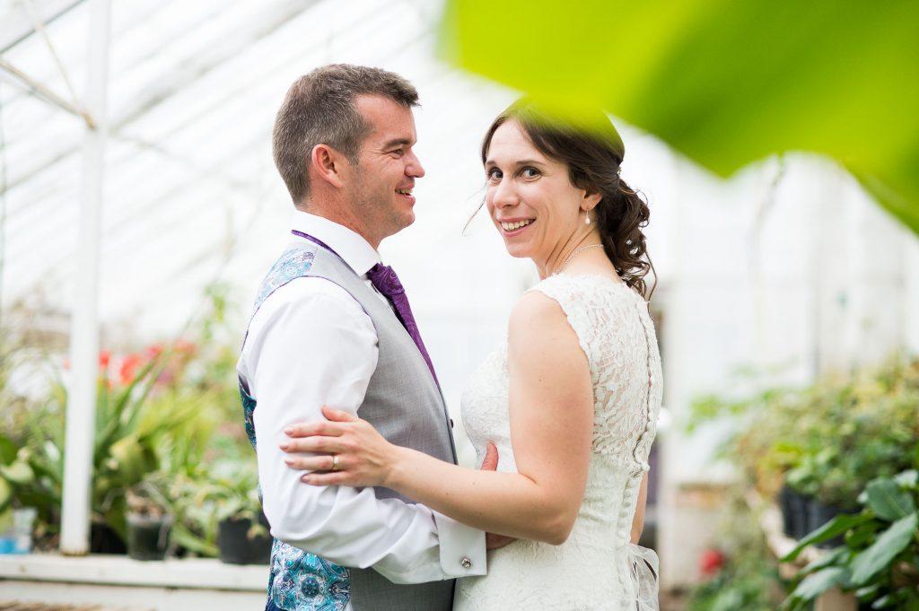 Smiling bride in greenhouse foliage Surrey wedding