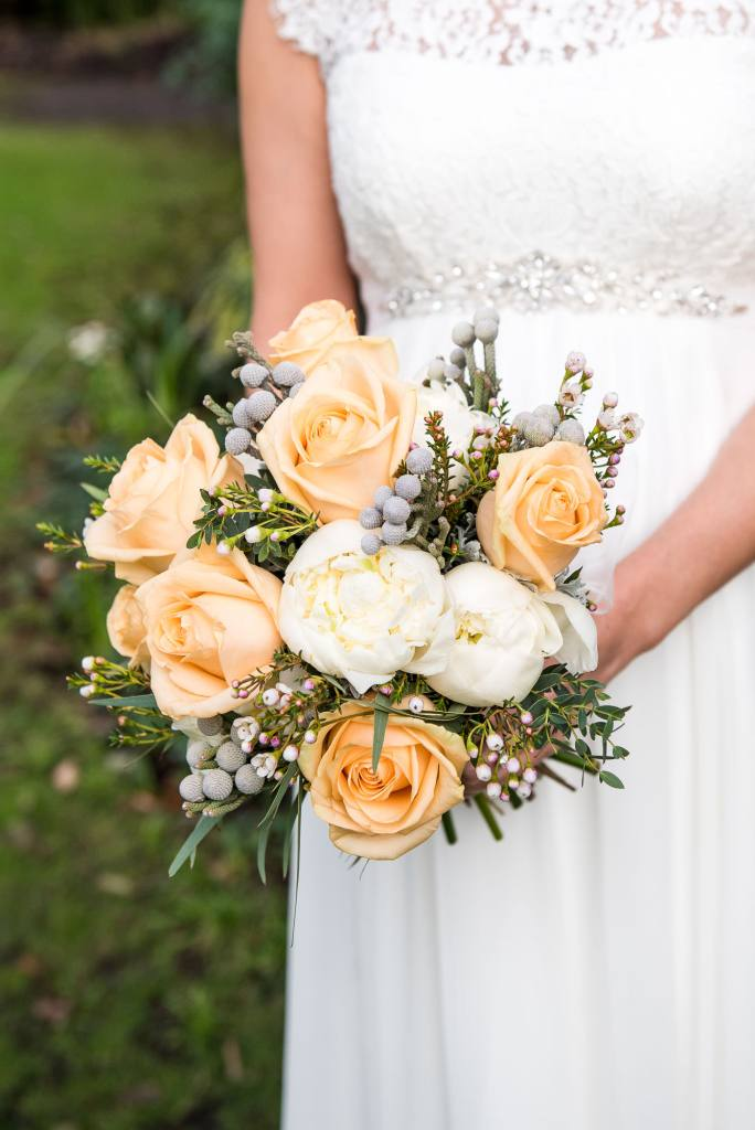 Fresh wedding bouquet with orange and white flowers