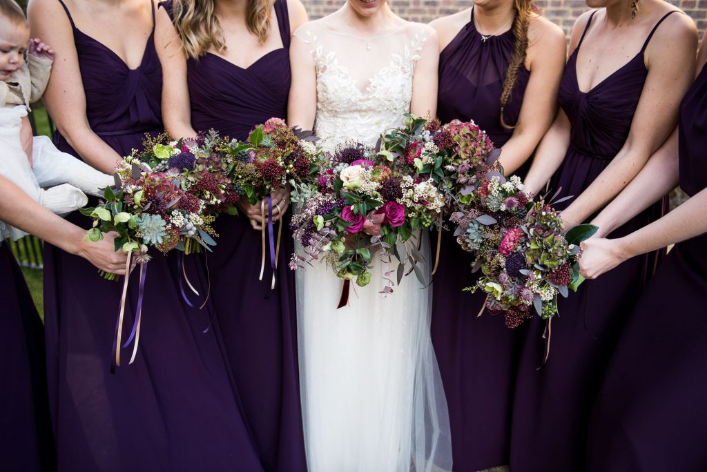 Ashridge House Wedding. Natural Wedding Photography. Bride surrounded by her bridesmaids with Winter wedding purple colours. Bouquets by Myrtle and Bloom.