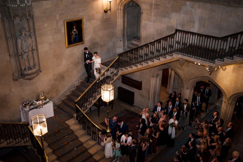 Ashridge House Wedding. Natural Wedding Photography. Couple walk down the grand staircase for their confetti line.