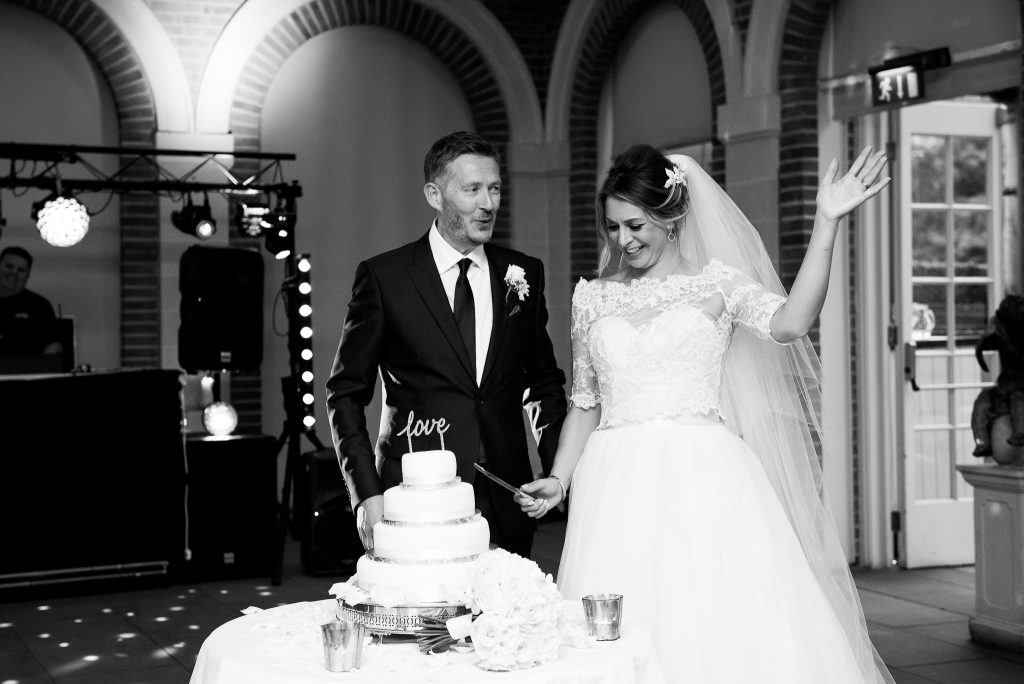 Great Fosters. Natural Documentary Wedding Photography, Surrey. The Bride and Groom Cut The Cake.