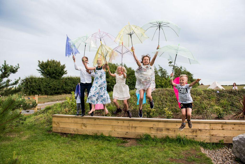 Inkersall Grange Farm Wedding - Same Sex Wedding Photography - Guests Play with Umbrellas atWedding Reception
