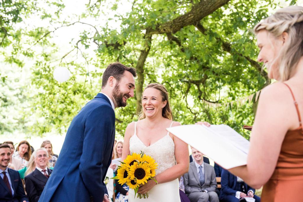 Outdoor Wedding Ceremony, Surrey Wedding Photography, Gorgeous Catherine Deane Bride and Groom Giggling and Happy During Wedding Ceremony