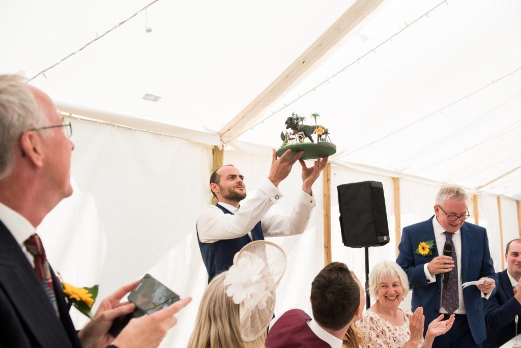 Outdoor Wedding Ceremony, Surrey Wedding Photography, Groomsmen Holds Up The Hand Made Wedding Present