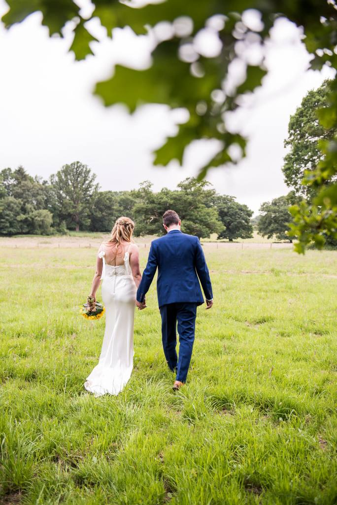 Outdoor Wedding Ceremony, Surrey Wedding Photography, Bride and Groom Walk Together In A Field