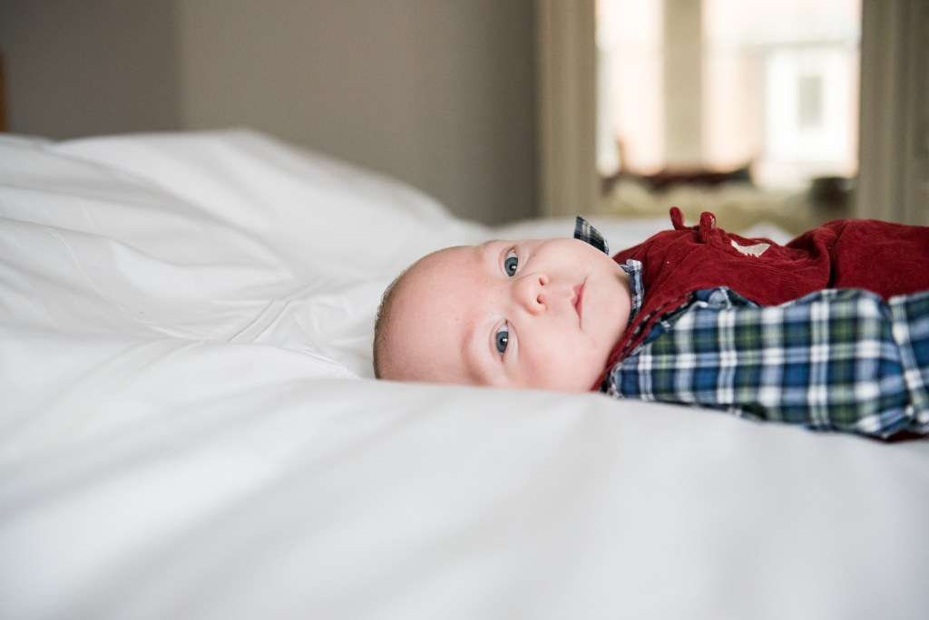 Newborn Photography Guildford, Christmas Family Shoot, Baby On The Bed Looking To Camera