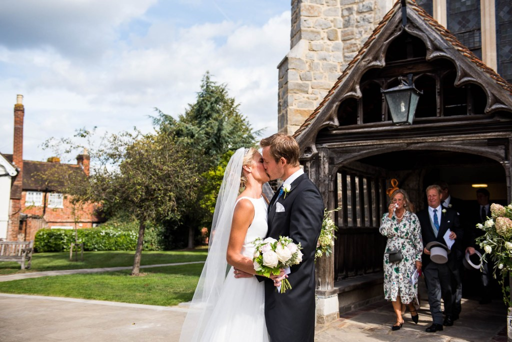 Outdoor Wedding Photography Surrey, Gorgeous Bride And Groom Share A Kiss Outside The Church