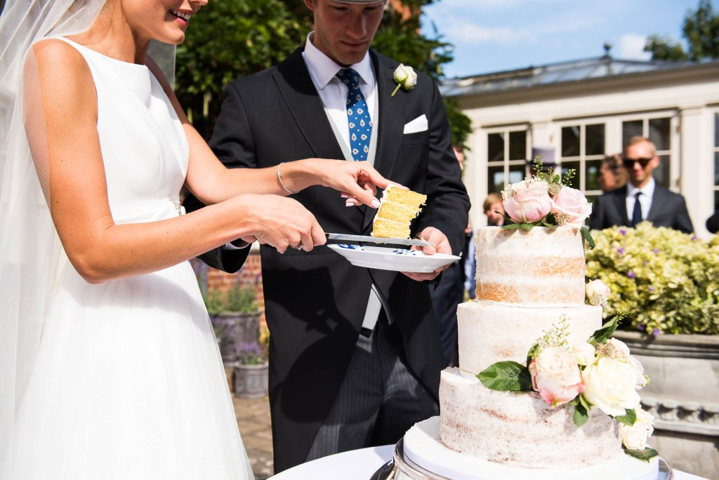 Outdoor Wedding Photography Surrey, Bride and Groom Cut Their Wedding Cake In The Sunshine Outside, Surrey Wedding Photography