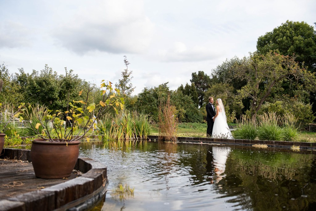 Outdoor Wedding Photography Surrey, Bride and Groom Stand by The Natural Pool