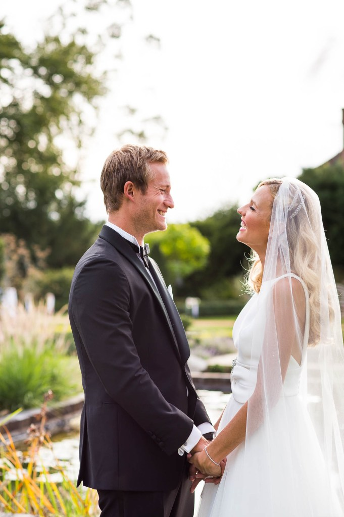 Outdoor Wedding Photography Surrey, Bride and Groom Stare Lovingly At Each Other Bathed in Golden Evening Light