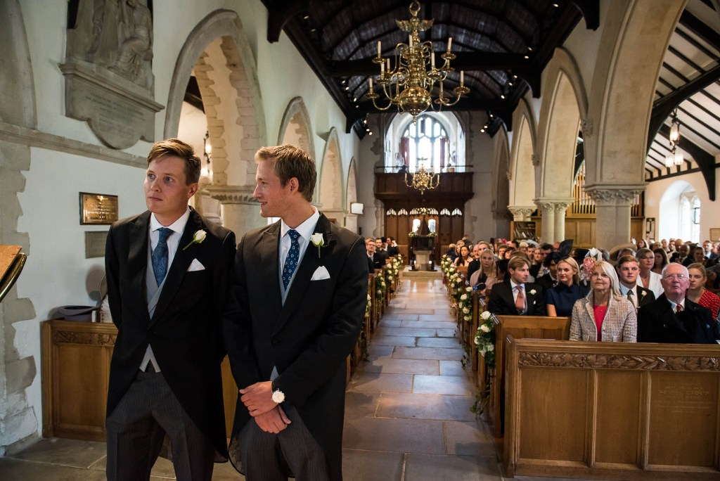 Outdoor Wedding Photography Surrey, Handsome Groom Waits Patiently For His Bride To Enter The Church