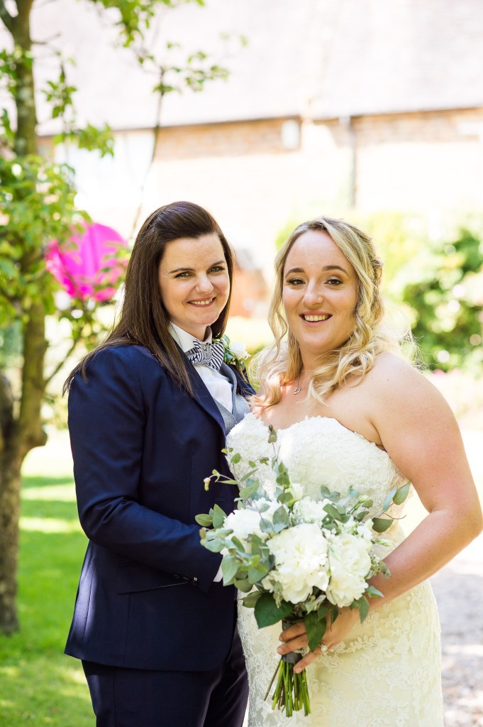 lgbt wedding photographer, brides in gorgeous blue suit with bow tie and one in strapless Maggie Sottero dress