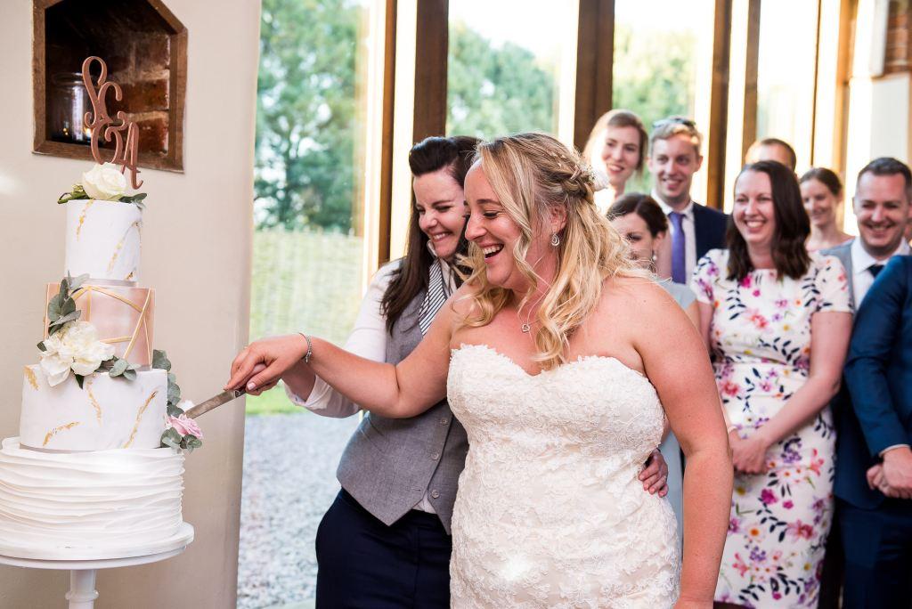 lgbt wedding photographer, brides cut the cake together, Dodmoor House Wedding