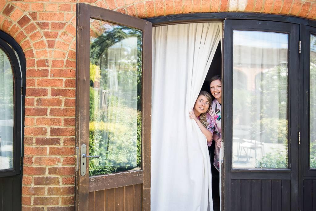 lgbt wedding photographer, Bridesmaids peering through curtains at Dodmoor House