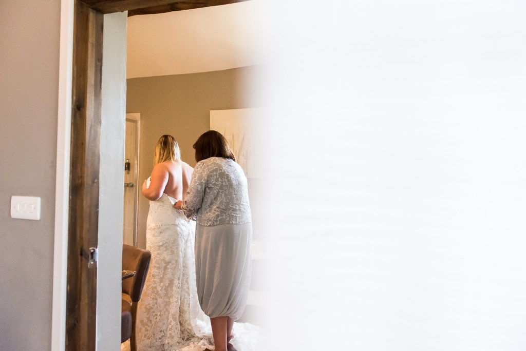 lgbt wedding photographer, Natural bridal photography, Mother helps her daughter into her wedding dress