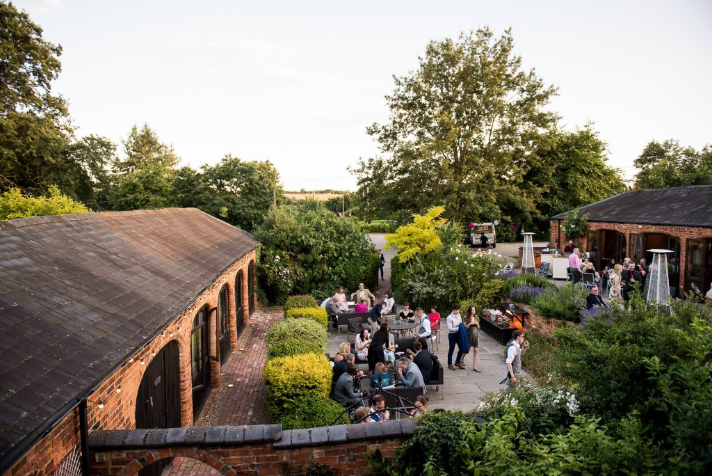 lgbt wedding photographer, wedding guests enjoy the courtyard on a summers evening at Dodmoor House