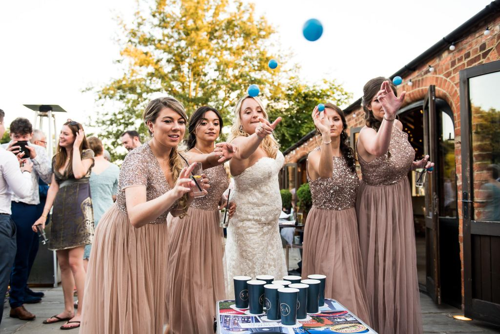 lgbt wedding photographer, bridal party in peach sequin dresses play beer pong at wedding reception