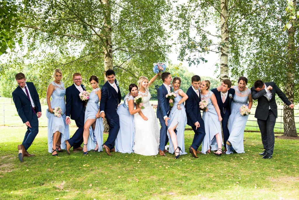 creative wedding photography surrey, bridesmaids and ushers arrange themselves with unique and silly poses