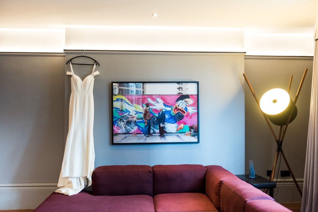 Old Marylebone Town Hall Wedding, Wedding dress hanging in an artistic room at the Andaz Hotel