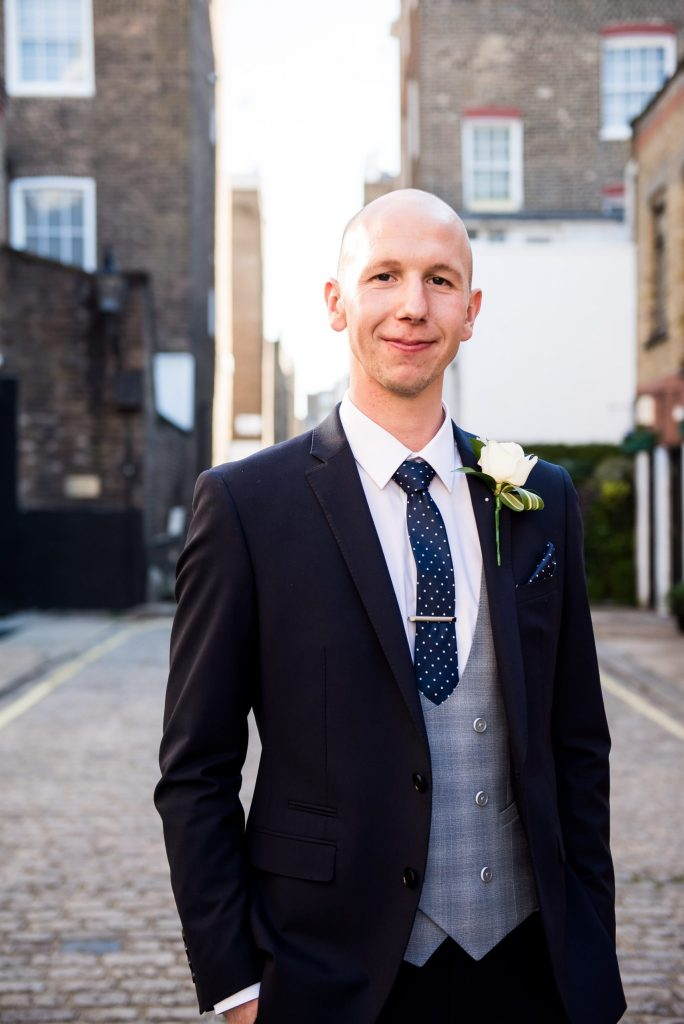 Old Marylebone Town Hall Wedding, handsome groom in three piece navy blue suit with grey waistcoat