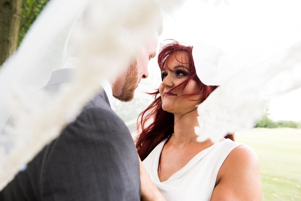 Alternative wedding photography - red haired bride and groom embrace under a veil