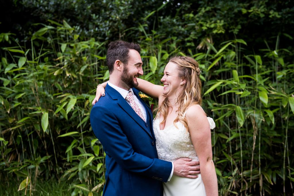 Alternative wedding photography - couple embrace in front of giant bamboo