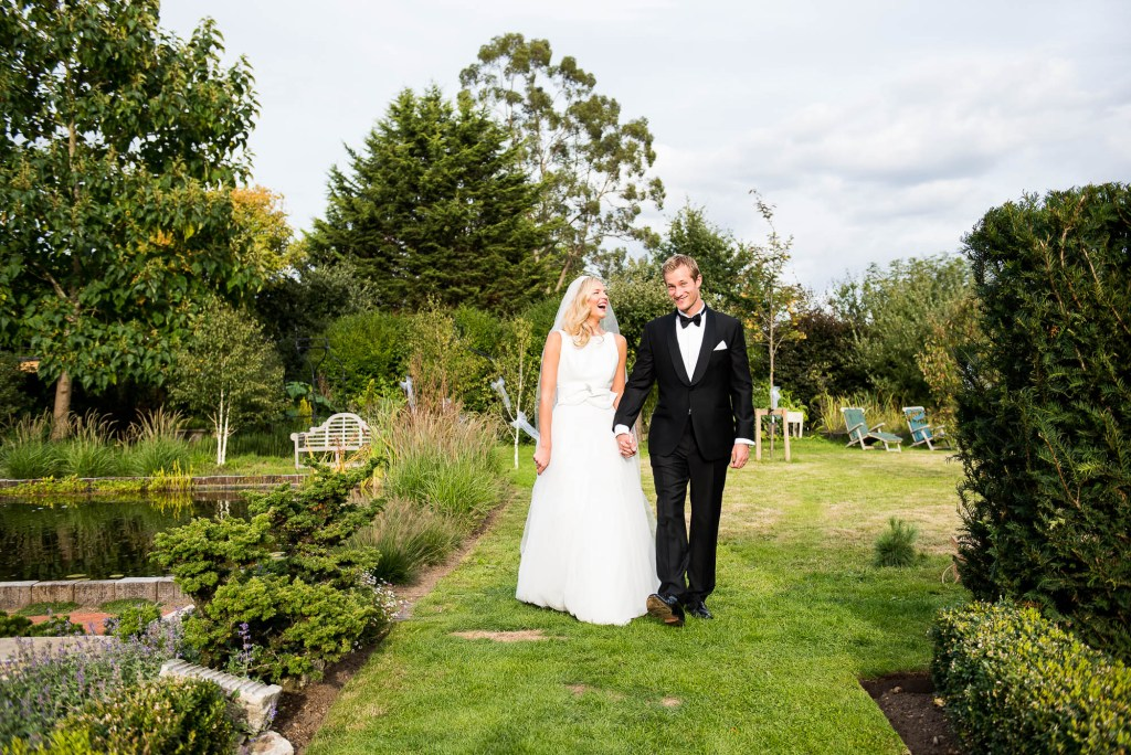 LGBT wedding photography, elegant bride and groom walk in gardens hand in hand
