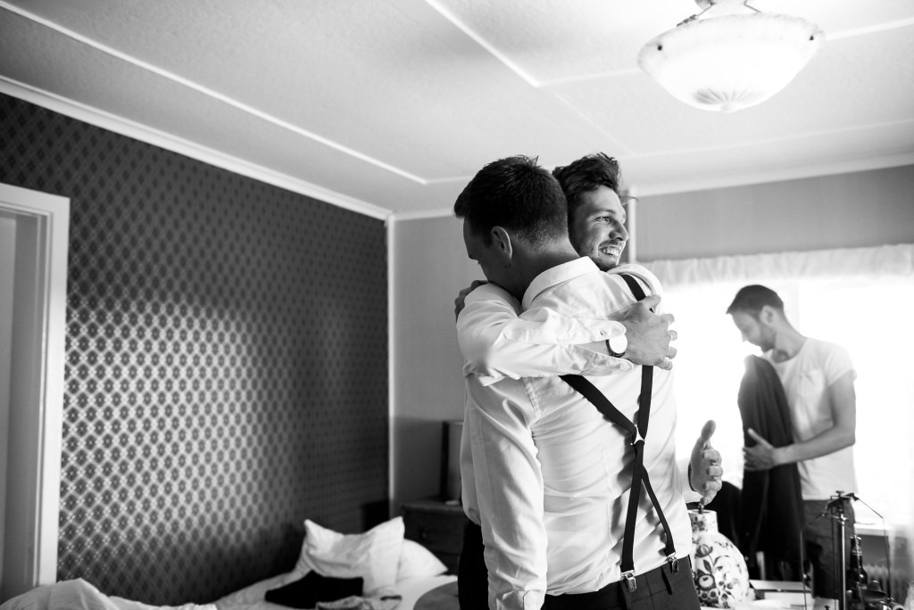 LGBT wedding photography, groom and best man share a hug