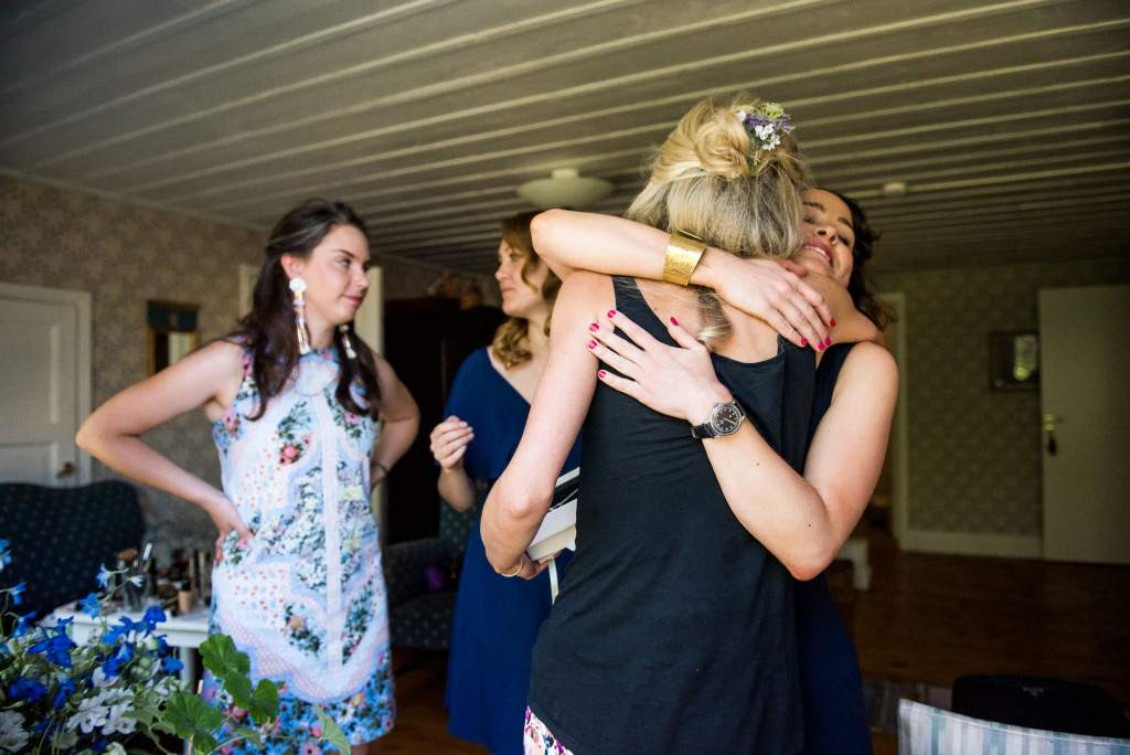LGBT wedding photography, bride is embraced with hugs from her bridesmaids
