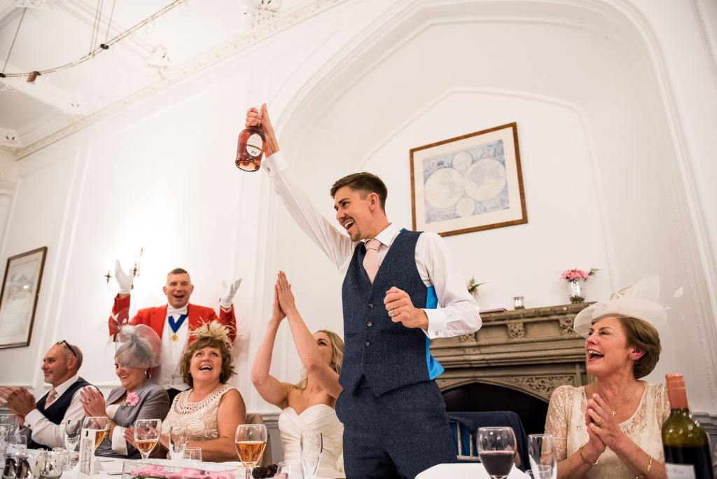 LGBT wedding photography, gay couple enbrace on the dance floor, groom raises a champagne bottle for wedding cheers