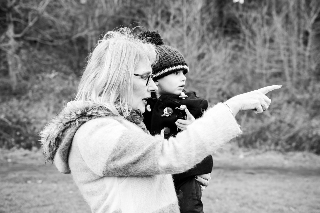 family photography guildford, black and white candid photograph of grandmother carrying her grandson