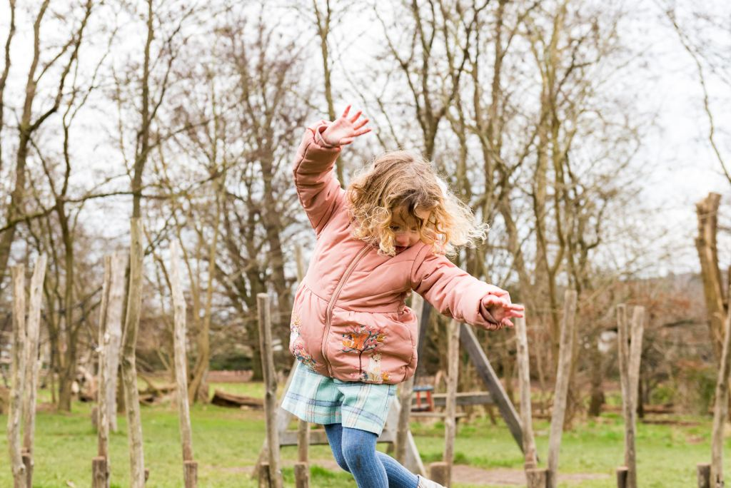 family photography guildford, little girl in cute pink jacket balances in the park