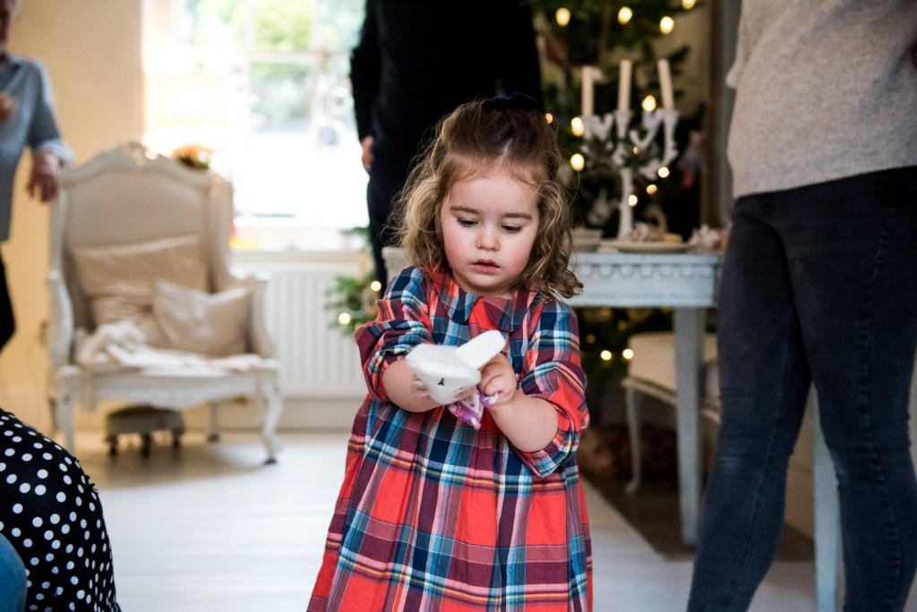 Little girl in red tartan dress puts on gloves