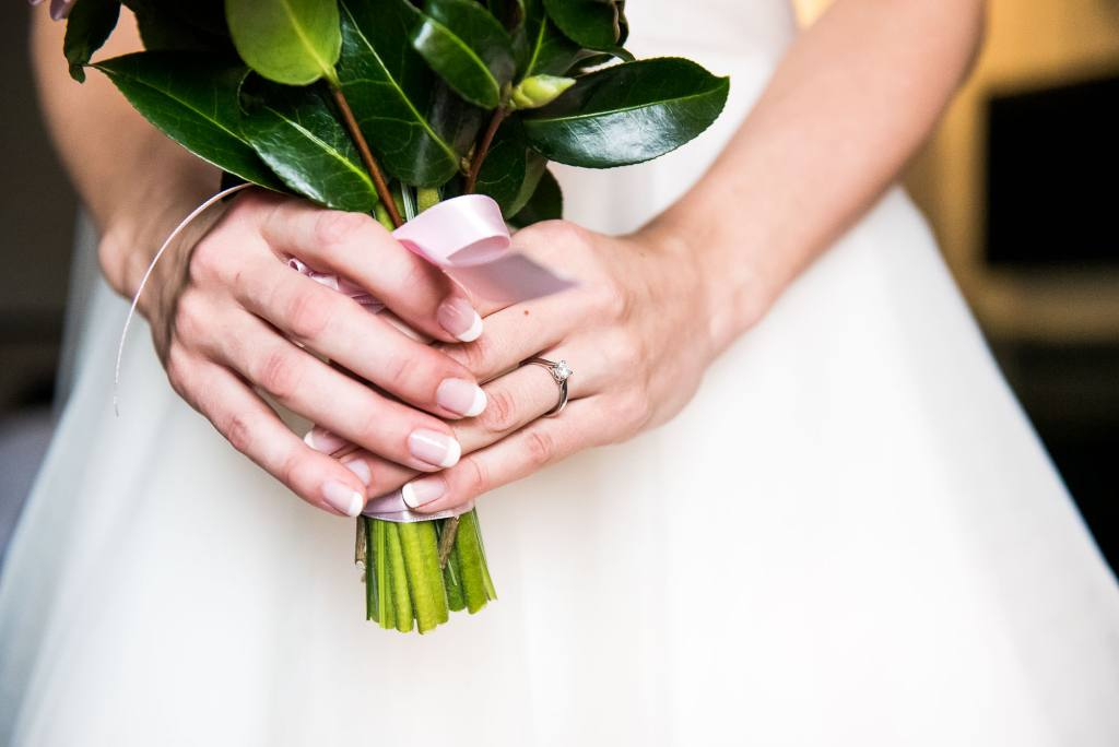 bride holds bouquet with engagement ring