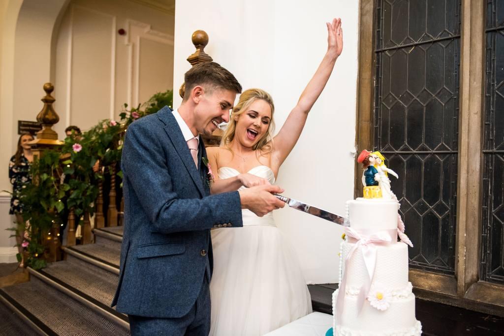 Horsley Towers wedding couple celebrate cutting the cake