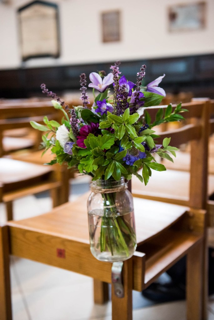 Purple, green and white ceremony flowers in rustic glass jars with twine
