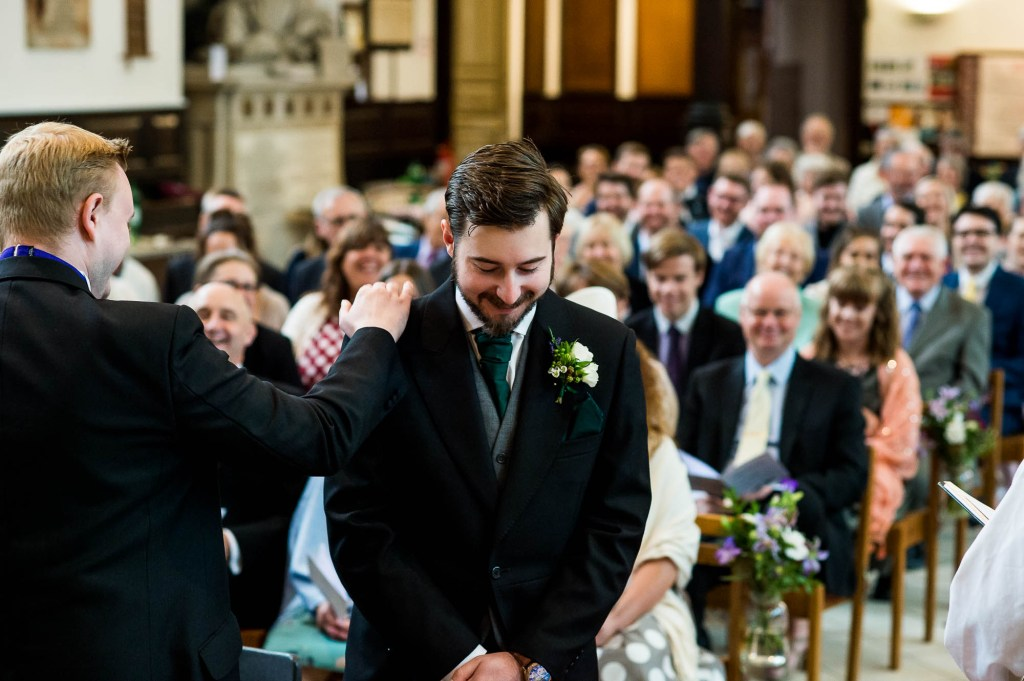 Groom waits at the alter and is comforted by his best man
