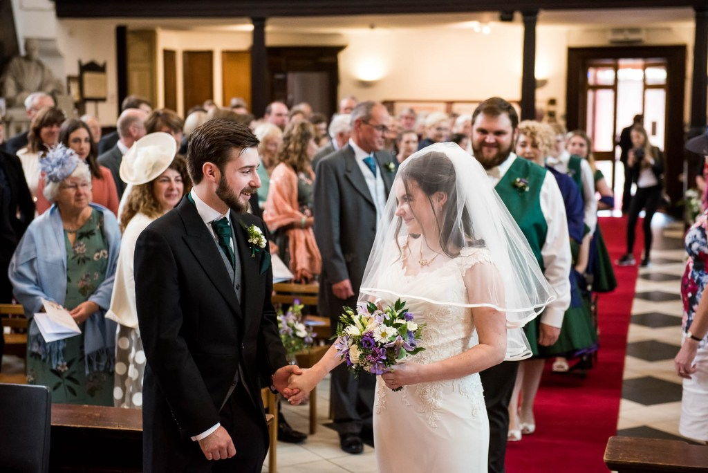 Bride takes groom's hand as she greets him at the top of the alter