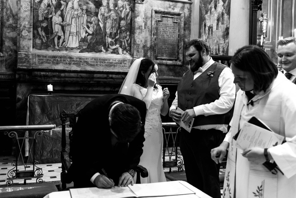 Candid and natural moment of the wedding party signing the register