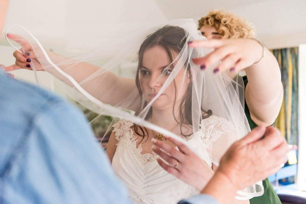 Bride in white lace dress is helped by her bridesmaid whilst putting on her veil
