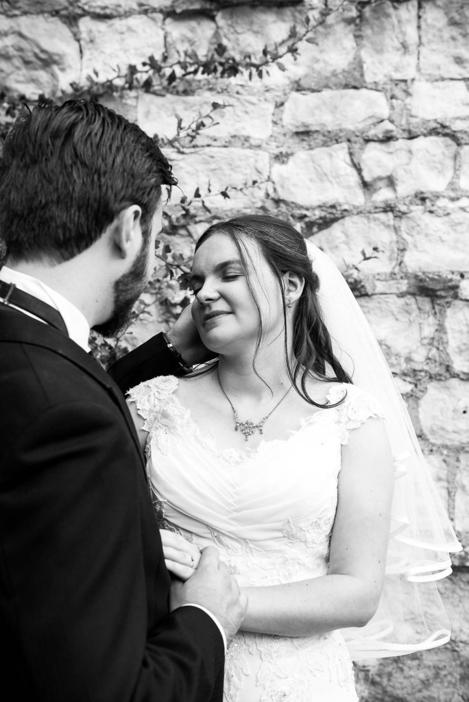 Black and white image of women with eyes closed and husband stroking her face, Documentary wedding photographer surrey