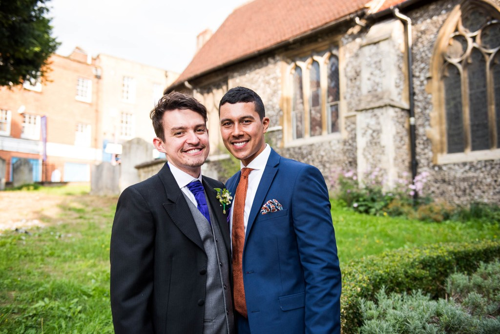 Same sex couple smile together outside church