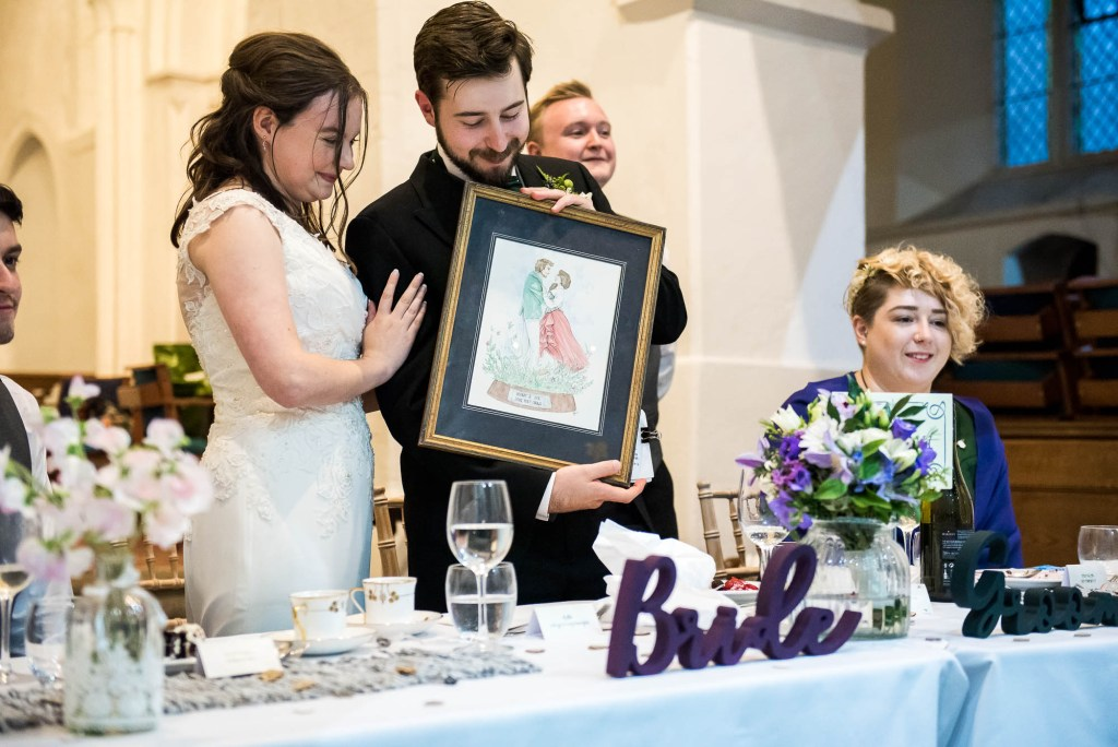 Documentary wedding photographer surrey, Bride and groom receive a personalised drawing as a wedding present