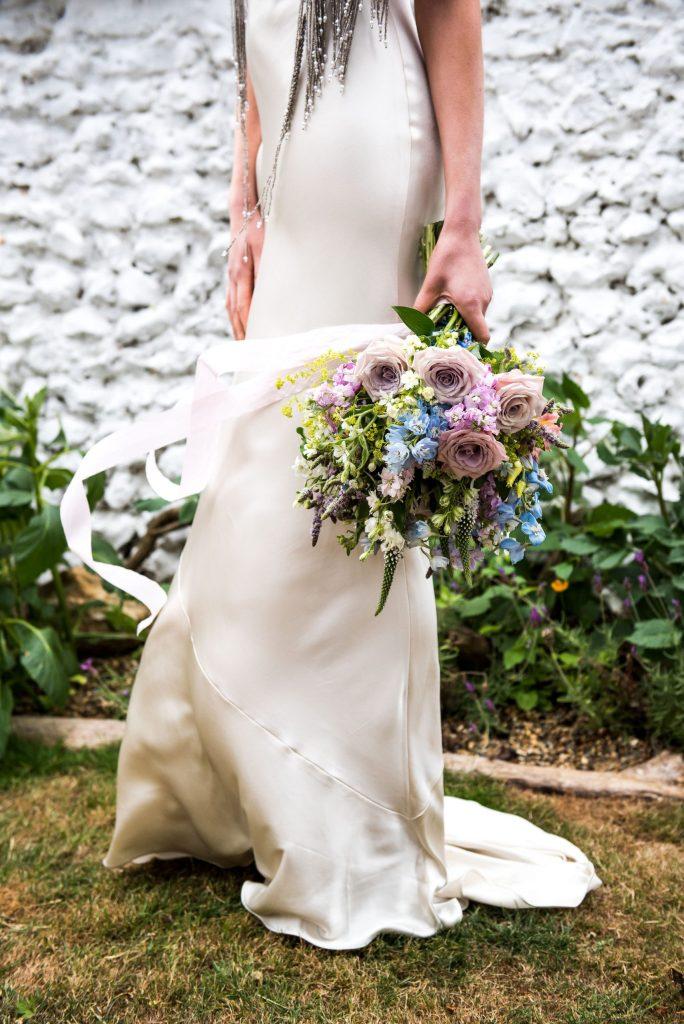 Surrey bride in a silk Pantiles wedding dress holding pastel coloured bouquet