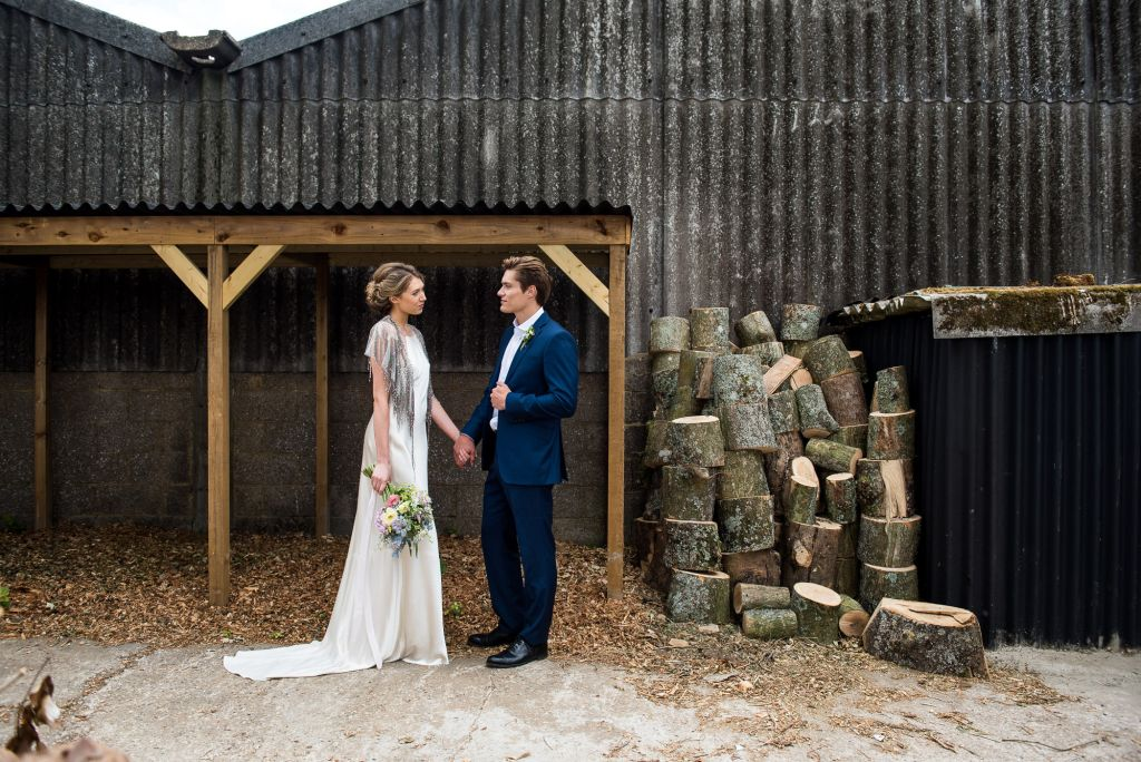 Couple stand in a rustic barn setting holding hands