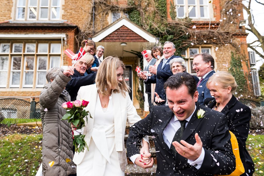 Scandinavian wedding guests wave Danish flags in confetti line Artington House wedding