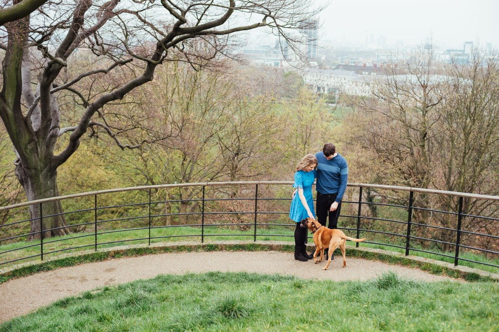 Couple greet a dog in Greenwich Park