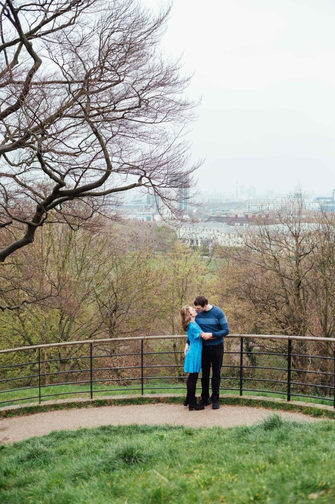 Engaged couple kiss with London city skyline as a backdrop