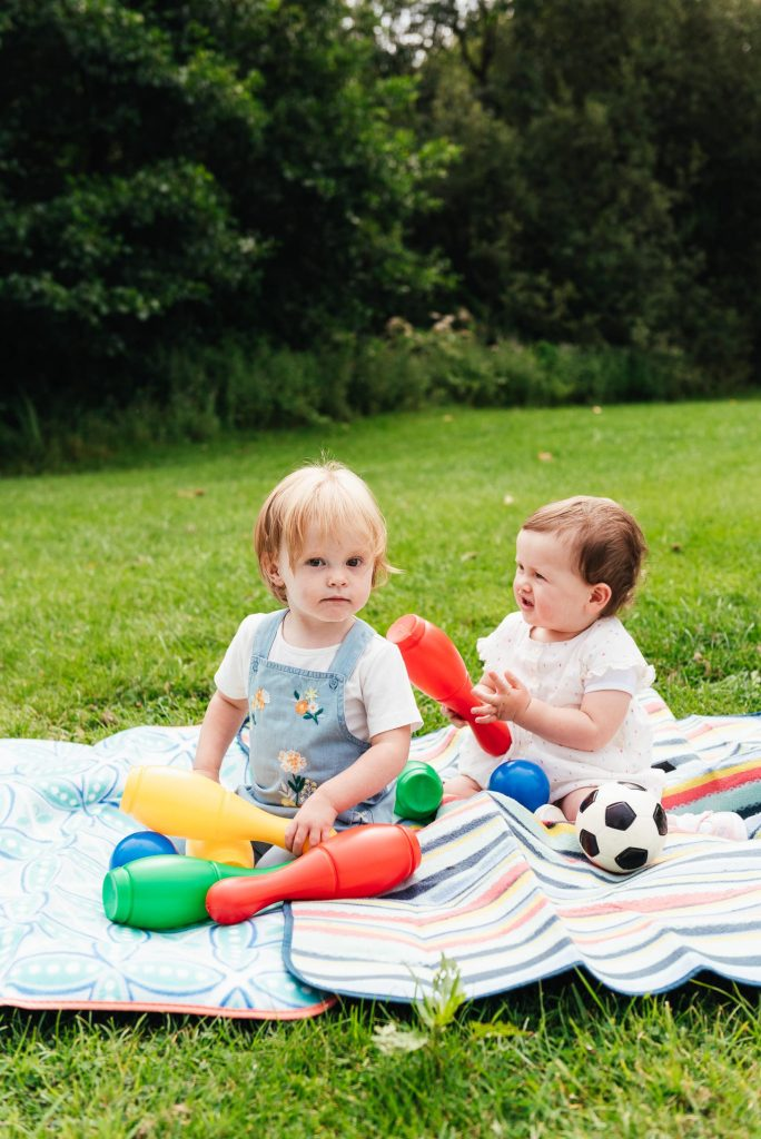 Toddlers play together with garden games in the sunshine